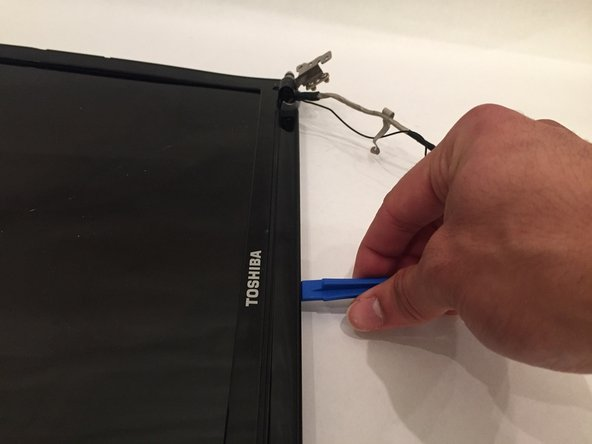 Using a prying tool, carefully pry along the edges of the screen cover