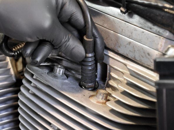 Image 1/2: Carefully remove the spark plug wire. Do not pull on just the wire, squeeze the spark plug boot, and pull it together with the wire.
