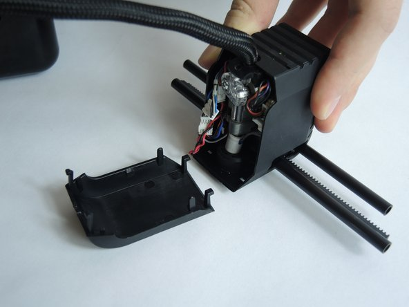 Slide the tracks off the second slider and remove the printer head and x-tracks from the center of the printer. To remove the front cover of the print head, firmly grip the cover and gently pull it off.