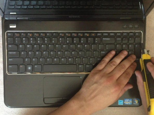 By using cutter, carefully lift up the one side of the keyboard and start opening the locking clips.