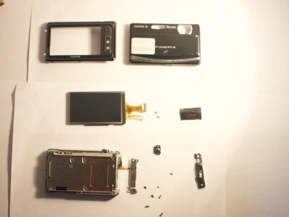 Using your index finger, guide the cable of the new screen into place. Lock it in by pushing the black level back down.