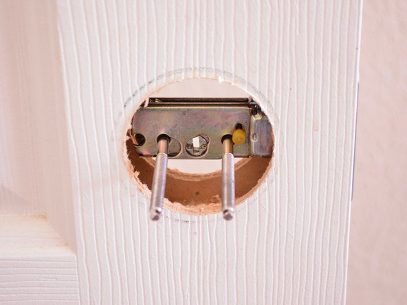 Image 2/3: Use a Phillips screwdriver to tighten the 2.5 inch mounting screws and secure the deadbolt to the frame.