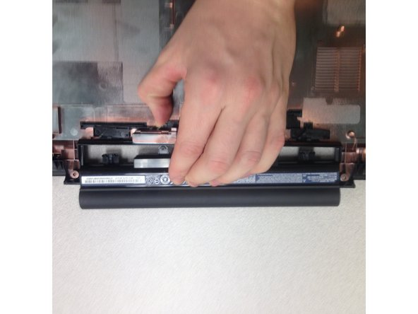 While holding the plastic lever, gently separate the battery from the bottom panel of the laptop.