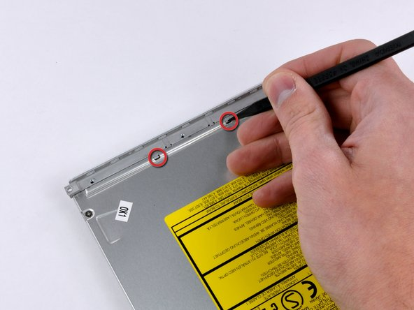 Image 1/1: Use a spudger to carefully depress the two tabs on top of the bezel.
