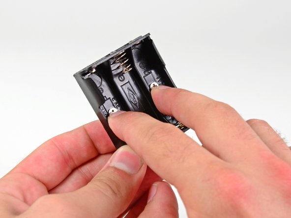 Image 1/2: Keeping your fingers on the screw heads to hold them in place, grab the battery compartment with your thumb and flip it over. The screw threads should protrude out of the top side of the battery compartment.