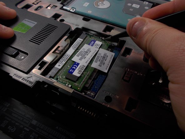 The first RAM card should pop up on its own. Gently remove this card, and look for the two strips of metal holding the bottom card down.