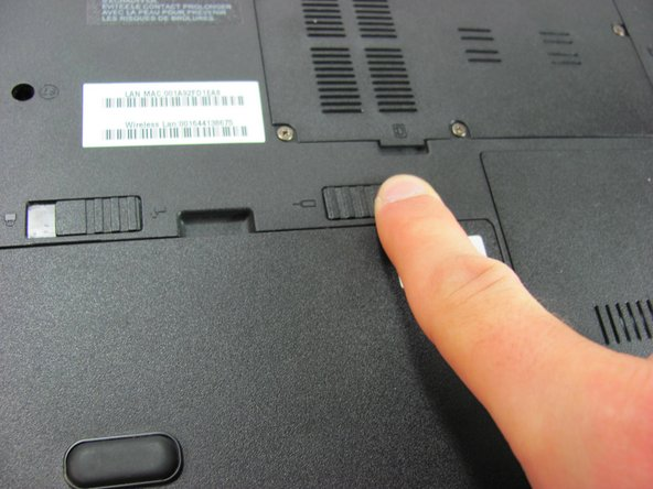The switch is spring loaded, so you must hold the switch in place while removing the battery.