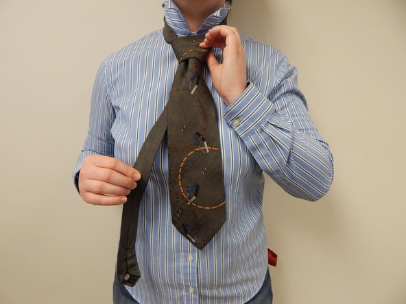 Tighten the neck loop by pulling down on the narrow end of the tie and sliding the knot up toward your neck.