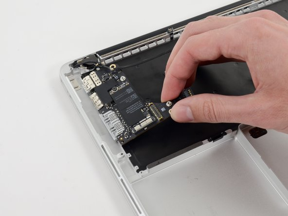 Image 2/2: Carefully pull and remove the I/O board away from its recess in the upper case.