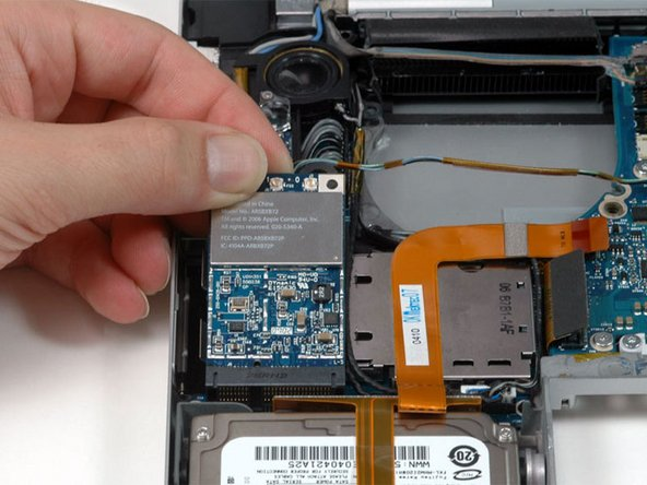 Lift the Airport Extreme card up and slide it out of its connector.