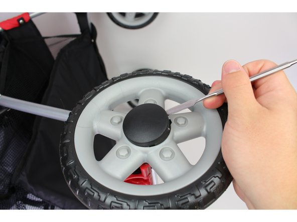 Use the spaded side of the metal spudger to pry off the small black hubcap on the     outside of the rear wheel.
