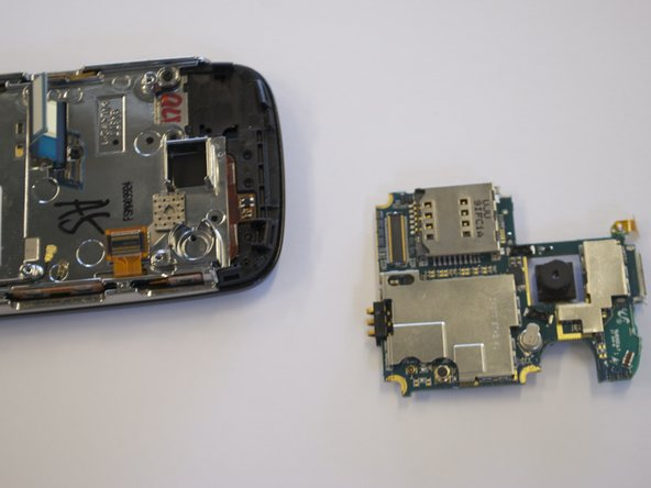 The circuit board will still be held on by a blue and black ribbon that is removed by gently pulling it upwards.