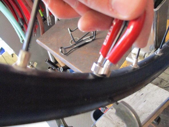 The nut you are tightening is screwing onto the spoke, so if you turn it counter-clockwise as you are looking down on it, you are tightening the spoke.