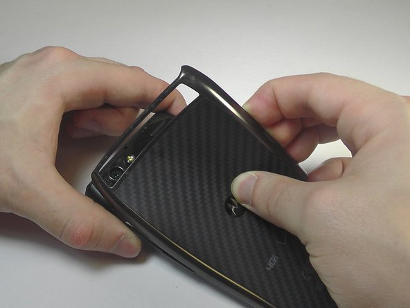 Image 1/3: The back cover is attached to the battery with a large amount of adhesive. Some force may be required to pull the back cover from the phone.