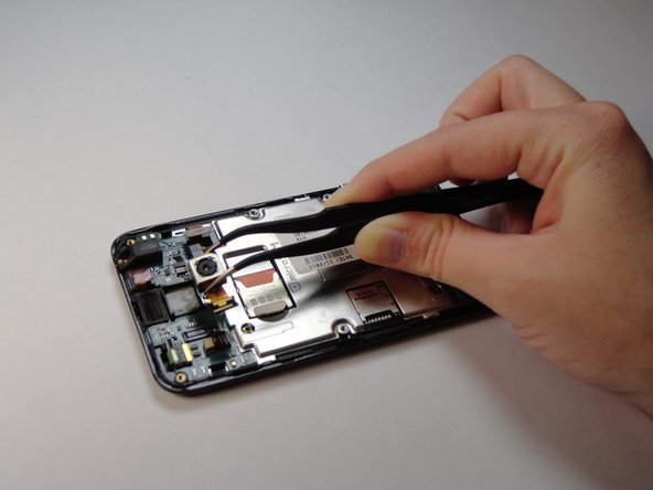 Use tweezers to remove the camera, you will need to use some force as it is glued on.