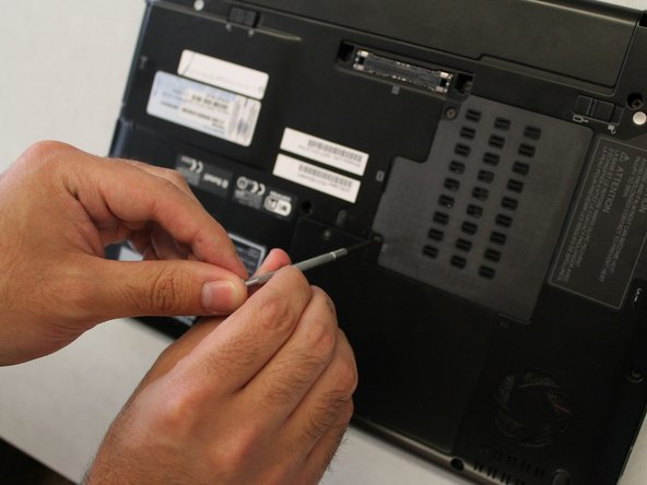 Using a Phillips #00 Screwdriver unscrew the 2 40mm screws  that are located on the plate covering the RAM.