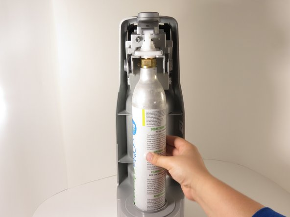 Image 1/2: Once the CO2 tank is free, pull it towards you and lift upwards to remove it from the device.