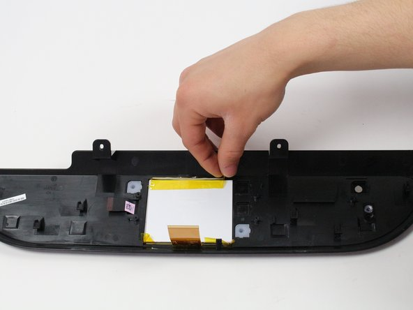 Insert the plastic opening tool between the white screen backing and the screen to pry the screen backing from the adhesive that holds it in place.