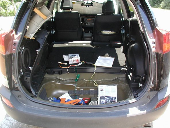 Remove the cargo area cover – emptying all the 'junk' and spare tire. The rear scuff panel and cargo tray on the driver's side are removed by popping the plastic rivets and metal bolts.