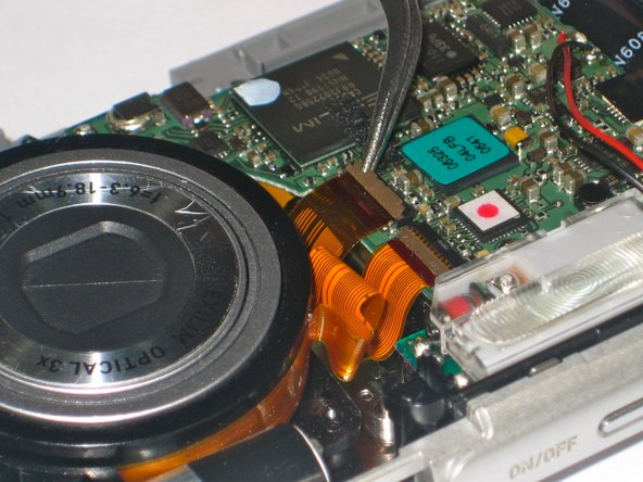 Using tweezers or finger nails to pull up the brown flaps where the three orange film strips meets the circuit board.