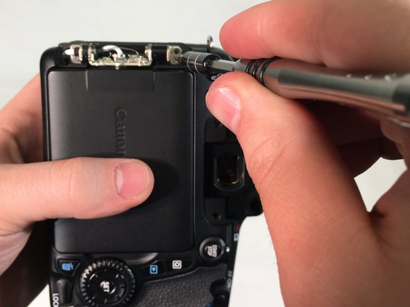 Remove two 4 mm Phillips #000 head screws that mount the LCD touchscreen to the hinge on the camera.