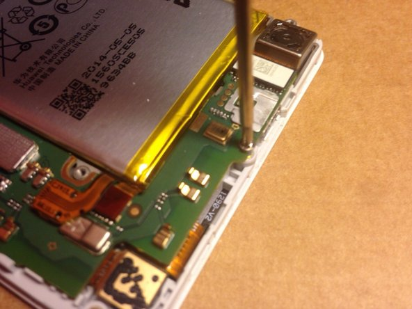 Image 3/3: Unscrew the screw holding down the motherboard at the bottom near the USB-port.
