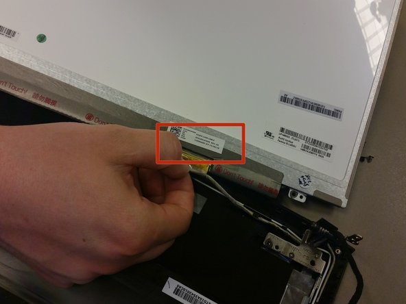 Image 1/3: On back of the LCD screen, locate the protective tape in the bottom right corner. Peel off the tape to reveal a latch with a connector cable.