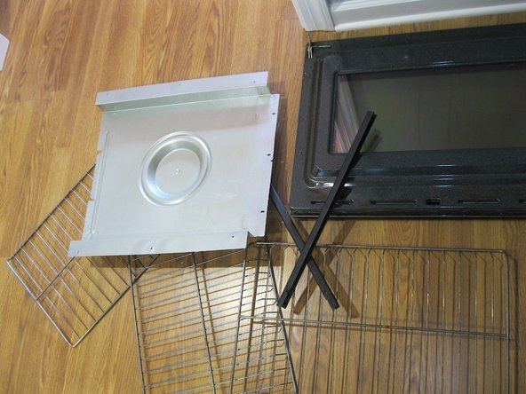 Each oven is secured to wall by two screws, one through each side mounting flange.  Remove.