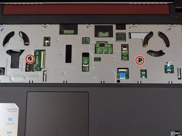 Locate the two screws  near the center of the laptop.