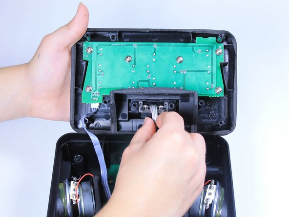 Remove the plastic casing, which encases the Apple lightning connector, from the top cover of the clock.