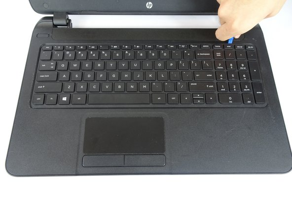 Use a plastic opening tool to pop out the  keyboard by starting at the top and working your way around the perimeter.