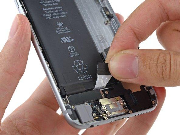 タブがバッテリーと背面ケースの間から抜け出るまでゆっくりと引っ張り続けます。タブからの抵抗感が増したとき、引っ張るのを止めて次の手順に移ります。