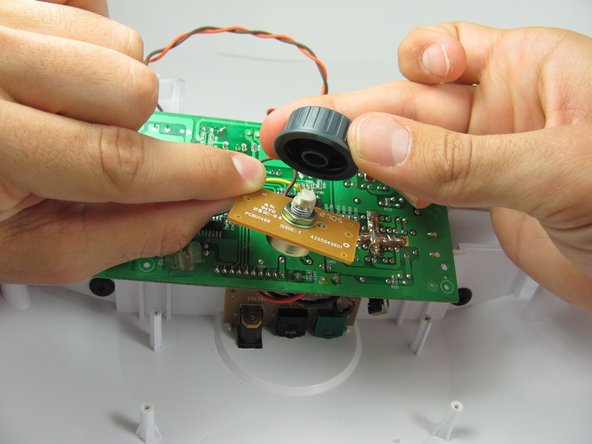 Hold the brown circuit board with one hand and the light intensity dial with two fingers of your other hand and carefully pull them apart.