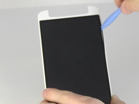 Insert the blue opening tool in between the black screen and the white border and slide it around the edge of the black screen.