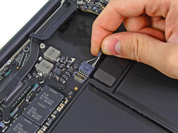 Image 1/1: Pull the cable parallel to the face of the logic board toward the right edge of the Air.