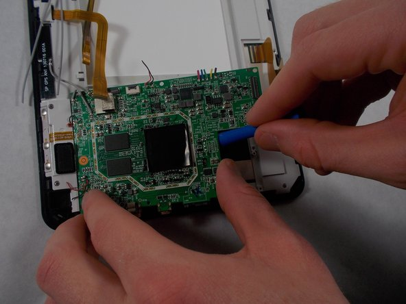 The motherboard is now free. Lift the motherboard with your hands or a plastic opening tool.