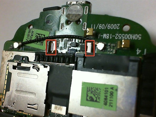 To remove the trackball, lay the circuit board face down and locate the two prongs as shown in the picture.