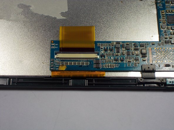 Image 1/3: Using the spudger tool, slide the black clip over the white housing up. This will release the ribbon cable.