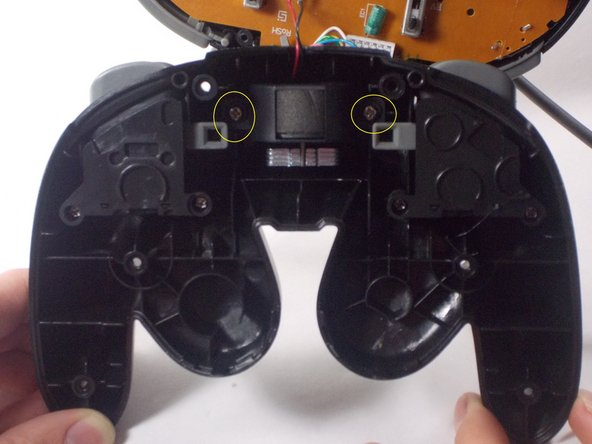 Next, open up the controller. You will notice the rumble motor is attached to the motherboard and to the bottom of the controller. Unscrew the rumble motor from the bottom of the controller.