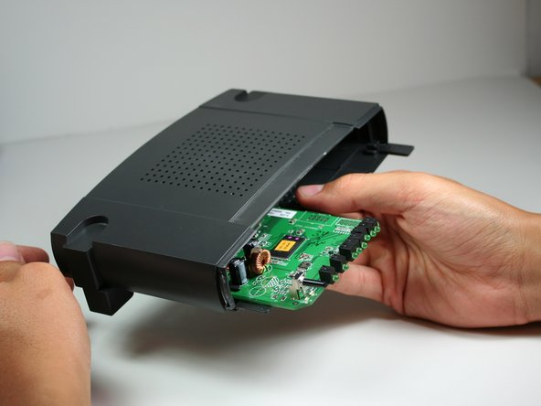 To remove the black casing that surrounds the green motherboard, slide the top half of the casing backwards. It only moves a very short distance.