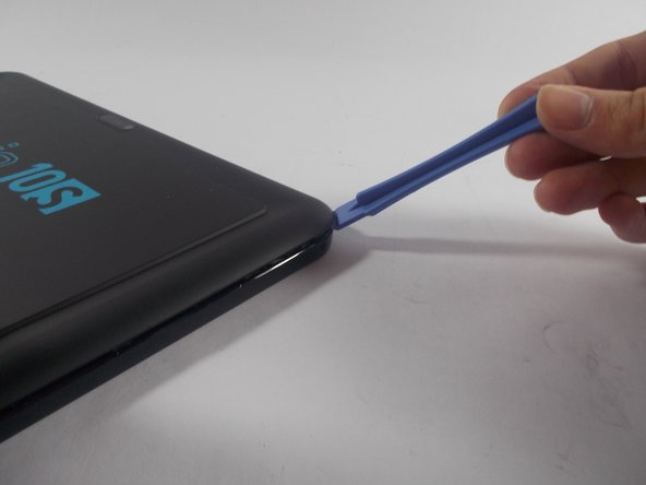 Image 1/1: Once the spudger is under the cover, slide it all the way around the device, pushing lightly into the device making sure it stays under the cover until all the clips are removed.
