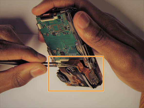 Once this has been done, use tweezers to unplug the flat topped connector for the lens' circuit board from the motherboard.