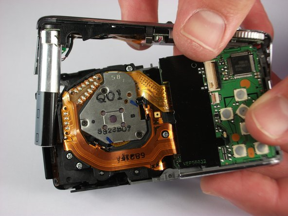 Carefully remove the upper assembly, which houses the buttons and the flash battery.
