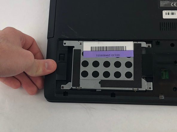 Slide the hard drive to the left, then remove it by lifting it from the compartment it is resting in.