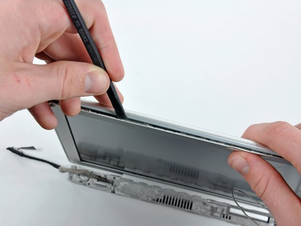 Insert a spudger between the top edge of the front display bezel and the plastic strip attached to the rear bezel, with the edge of the tool angled toward the LCD.