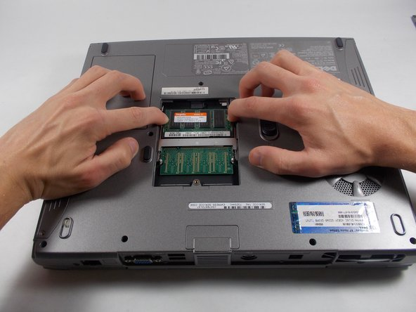 Use your hands to pull the two metal tabs away from the RAM.