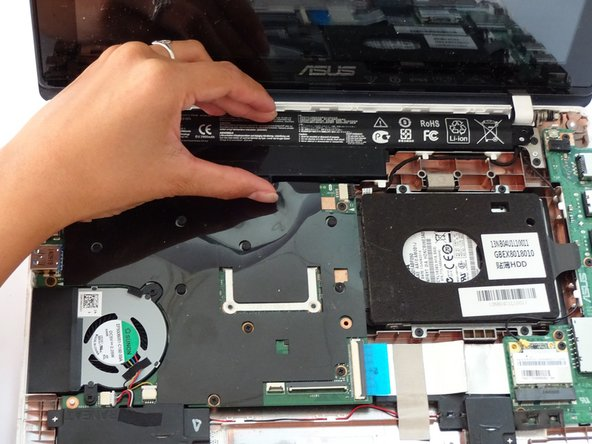 Gripping the wider left section, lift the battery up and away from computer.