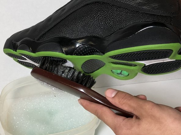 Use a soft bristle brush with the soap and water mixture to scrub dirt from bottom of shoe.
