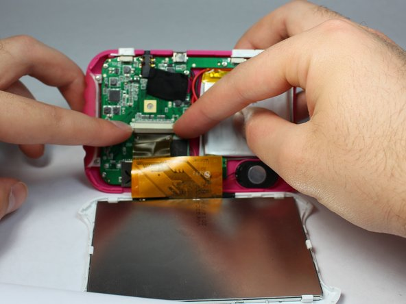 Disconnect the LCD cable from the motherboard by pressing together the two sides of the clamp to separate the device into two.