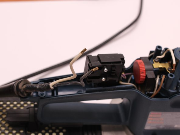 Using the 2.5 mm Flathead Screwdriver, loosen the two screws securing the white and black wires to the On/Off Switch.